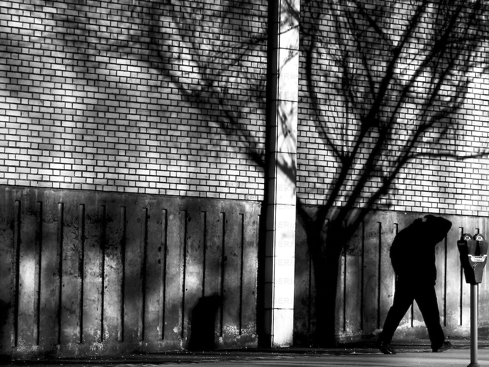 A male figure walking along a path by a building