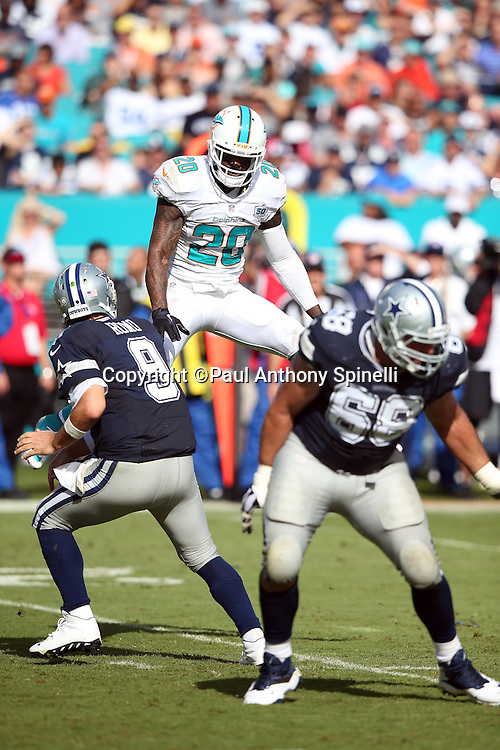 Miami Dolphins strong safety Reshad Jones (20) leaps in the air while chasing Dallas Cowboys quarterback Tony Romo (9) on a pass play whileDallas Cowboys tackle Doug Free (68) blocks during the 2015 week 11 regular season NFL football game against the Dallas Cowboys on Sunday, Nov. 22, 2015 in Miami Gardens, Fla. The Cowboys won the game 24-14. (©Paul Anthony Spinelli)