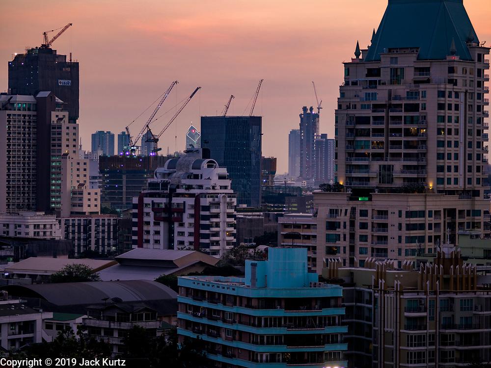 08 MARCH 2019 - BANGKOK, THAILAND: Construction cranes dot the skyline at sunset over Bangkok as seen from the EmQuartier, an upscale mall on Sukhumvit Rd.    PHOTO BY JACK KURTZ