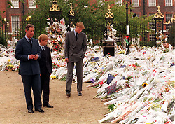 File photo dated 5/9/1997 of the Prince of Wales and his sons Prince William (right) and Prince Harry, view the sea of floral tributes to Diana, Princess of Wales, at Kensington Palace. The Princes on Wednesday viewed tributes attached to the Golden Gates of the Palace in London ahead of the 20th anniversary of their mother's death.