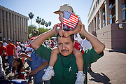 Apr. 19, 2009 -- PHOENIX, AZ: A man carries his son and an American flag during a march in central Phoenix Sunday. About 2,000 people marched from the Arizona State Capitol to Cesar Chavez Plaza in downtown Phoenix. The march was organized by the United Farm Workers of America to promote immigration reform.  Photo by Jack Kurtz