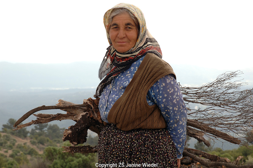 Woman coming up from the field in hillside by small village in Southern Turkey.