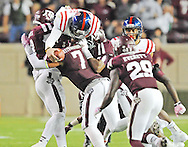 Mississippi Rebels quarterback Bo Wallace (14) gets a first down over Texas A&M Aggies running back Trey Williams (3), Texas A&M Aggies linebacker Jordan Mastrogiovanni (7), and Texas A&M Aggies defensive lineman Jarrett Johnson (40) in College Station, Texas on Saturday, October 11, 2014. Ole Miss won 35-20 to improve to 6-0.