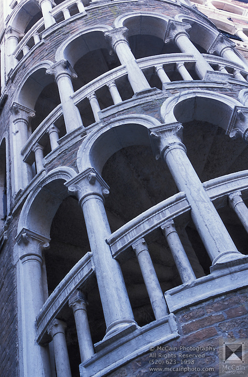 Exterior view of a spiral staircase at the Palazzo Contarini del Bovolo (also called Palazzo Contarini Minelli dal Bovolo). The Palazzo Contarini del Bovolo is a small palace in Venice, best known for the external spiral staircase with a plethora of arches, known as the Scala Contarini del Bovolo (of the snail). The palace dates from the 15th century and is apparently in poor state of restoration, while the staircase leads to an arcade provides a charming panoramic vista over some of the roof-tops of the city. The palace is located in a less-traveled side-street near the Campo Manin, near the Rialto...Subject photograph(s) are copyright Edward McCain. All rights are reserved except those specifically granted by Edward McCain in writing prior to publication...McCain Photography.211 S 4th Avenue.Tucson, AZ 85701-2103.(520) 623-1998.mobile: (520) 990-0999.fax: (520) 623-1190.http://www.mccainphoto.com.edward@mccainphoto.com.