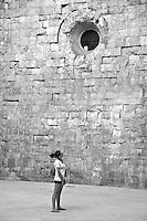 Castel del Monte - Puglia - Visitatori. Castel del Monte è un edificio del XIII secolo costruito dall'imperatore Federico II in Puglia, nell'attuale frazione omonima facente parte del vicino comune di Andria. Inserito nel 1996 tra i monumenti patrimonio dell'Unesco, Castel del Monte conserva da secoli il mistero della sua funzione. La forma a pianta ottagonale ha ispirato le più diverse ipotesi sul motivo della sua costruzione: scartata la funzione di torretta di difesa (per la mancanza di strutture militari e delle scale a chiocciola costruite in senso antiorario, a svantaggio dei soldati costretti a impugnare le armi con la mano sinistra), scartata la funzione residenza di caccia a causa della mancanza di stalle, si accredita la funzione di tempio, anche per via dei simboli che caratterizzano l'intera costruzione.