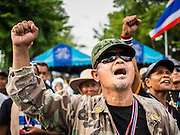 16 MAY 2014 - BANGKOK, THAILAND: A man cheers for anti-government leader Suthep Thaugsuban in front of the parliament complex in Bangkok. Thousands of protestors from the People's Democratic Reform Committee (PDRC) surrounded the Thai Parliament complex Saturday to pressure the Thai Senate to select an interim Prime Minister to replace ousted former PM Yingluck Shinawatra. The Senate decided not to appoint an interim PM of their own and announced a meeting with the current interim Prime Minister. The protestors left the parliament complex and threatened to return in larger numbers if the Senate doesn't act. The Senate appointment of an acting PM could plunge Thailand into chaos since there is already an interim Prime Minister from the ruling Pheu Thai party.     PHOTO BY JACK KURTZ