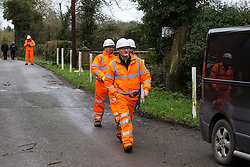 Harefield, UK. 14 January, 2020. Men wearing HS2 overalls pass along a road close to a protection camp from which Stop HS2 activists are being evicted. Part of the nearby Colne Valley protection camp was evicted by bailiffs last week. 108 ancient woodlands are set to be destroyed by the high-speed rail link and further destruction of trees for HS2 in the Harvil Road area is believed to be imminent.