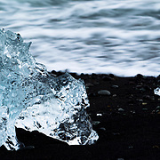 Clear iceberg chunk on the black sand beach of Jokulsarlon, Iceland
