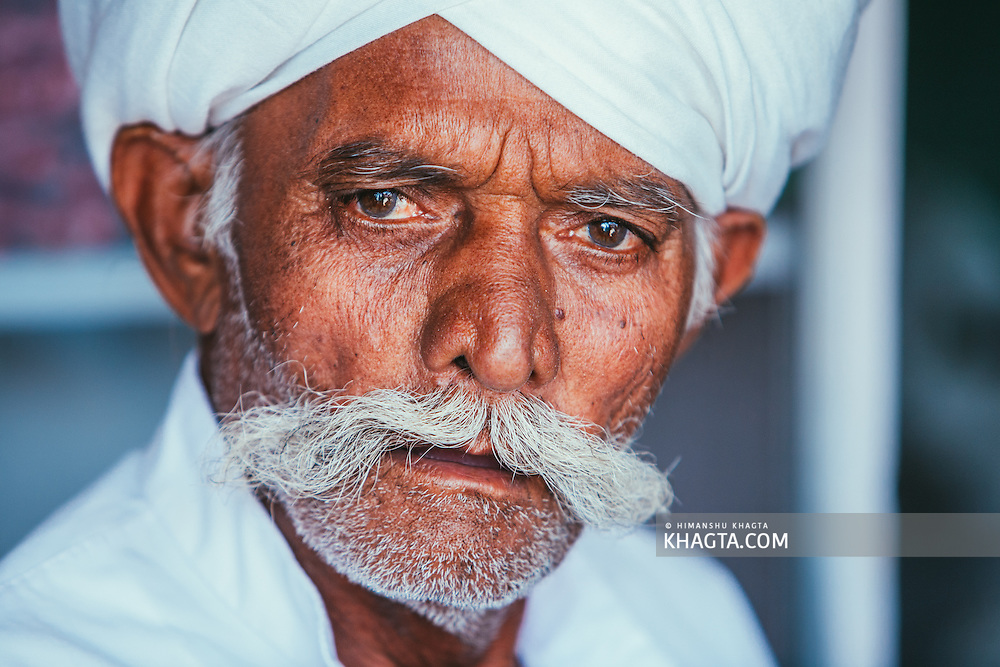 Portrait of an ethnic Rajasthani man with a mustache  wearing white clothes and a turban.
