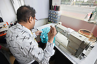 Back view of male tailor stitching cloth while sitting at sewing machine
