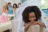 Bride wearing veil with friends at bridal shower