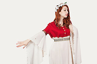 Sad young woman in old-fashioned princess costume looking away against gray background