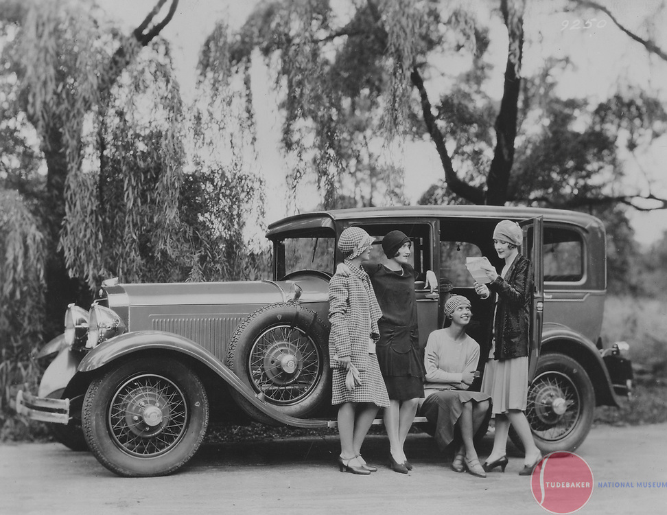 A quartet of young ladies stand near a 199 Studebaker Commander FD Regal Sedan