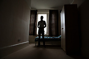 An unaccompanied minor refugee child stands alone in his bedroom where he has been recently housed. United Kingdom. Housing conditions are often a little bare and bleak for new arrivals. (photo by Andrew Aitchison / In pictures via Getty Images)
