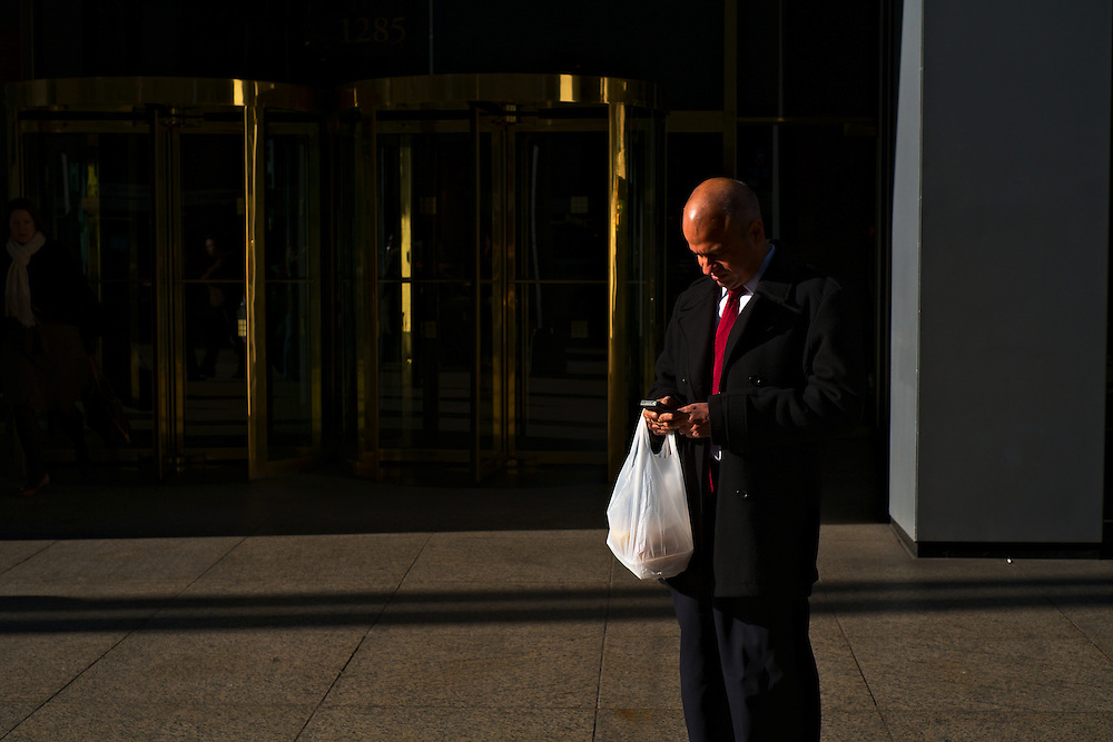 Man with iPhone and shopping bag