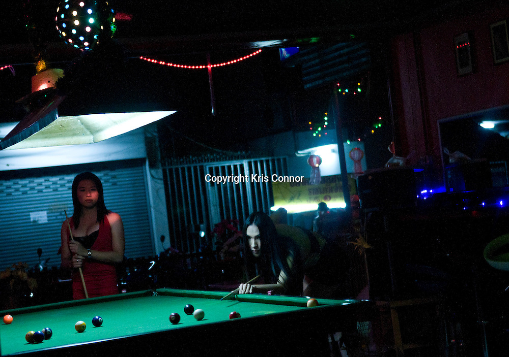 Two women play pool at a bar in Chiang Mai, Thailand. Photo by Kris Connor