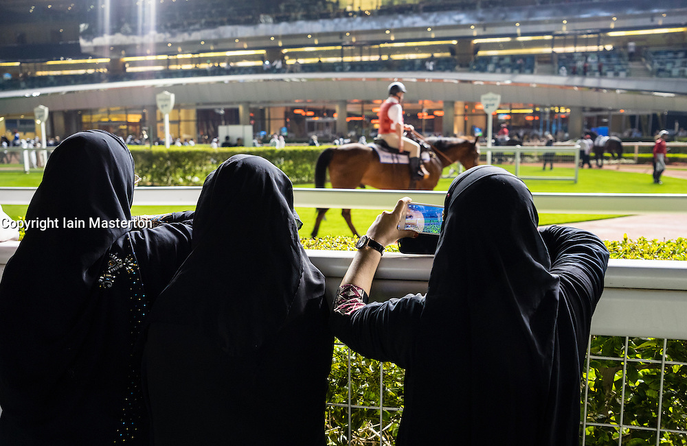Women in black abayas at parade ring at horse racing meeting at Al Meydan racecourse at night in Dubai United Arab Emirates