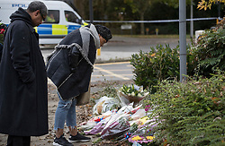 © Licensed to London News Pictures. 10/11/2016. Croydon, UK. People look at floral tributes placed near the overturned tram at Sandilands station. Investigations are continuing into a tram crash that police say claimed seven lives and injured 50. The driver has been arrested and is being questioned by police. Photo credit: Peter Macdiarmid/LNP