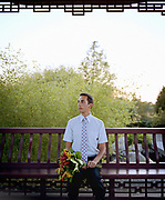 Young man sitting on park bench, holding bouquet of lilies