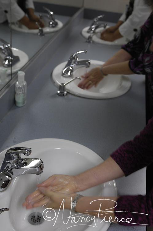 Women wash their hands in an office restroom after using the toilet.