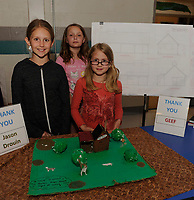 4th graders Mia Burlock, Ally Onos and Alyssa McKenna show their model of Bolduc Farm's sugar shack with building plans behind them for their STEAM project at Gilford Elementary School on Tuesday evening.  (Karen Bobotas/for the Laconia Daily Sun)