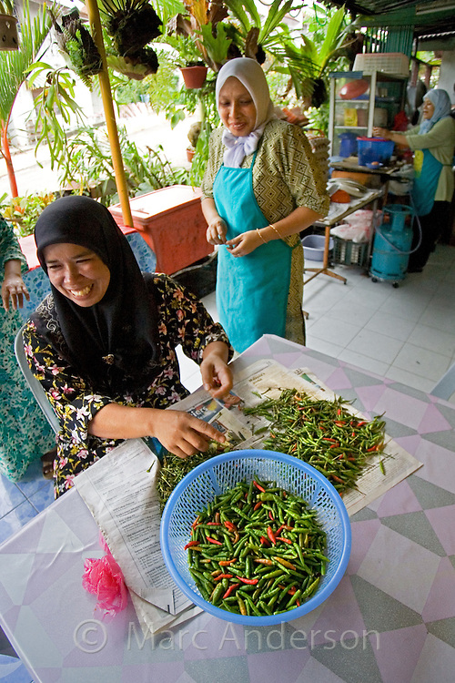 A Malaysian muslim woman preparing chillis outside a restaurant in Jerantut, Malaysia.