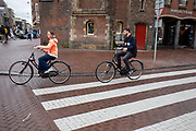 Een man en een vrouw rijden op een huurfiets over het Muntplein in Amsterdam.<br /> <br /> A man and a woman ride at the Munt Square in Amsterdam on a rental bike.
