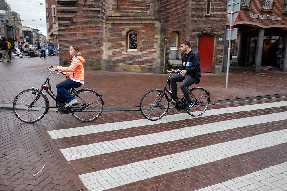 Een man en een vrouw rijden op een huurfiets over het Muntplein in Amsterdam.<br /> <br /> A man and a woman ride at the Munt Square in Amsterdam on a rental bike.
