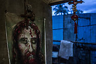 Religious icons guard the front door of 84 year old, Remy Fernandez, whose youngest son, Juan, was killed by masked gunmen in his home while preparing dinner.  They came through this door.  Remy had urged him to go into hiding but Juan insisted on preparing a spaghetti dinner on one of his daughter's birthday.  Juan's wife is in prison on drug charges.  So, Remy is left with the task of raising 7 grandchildren in this impoverished community on the fringes of a city dump in Payatas.  Metro Manila, Philippines.