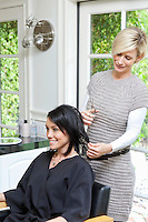 Beautiful happy woman getting a haircut from a mature hairstylist in beauty salon