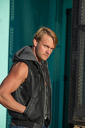 mysterious and devious blond man in a sleeveless leather jacket