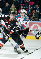 KELOWNA, CANADA, JANUARY 1: Cole Martin #8 of the Kelowna Rockets checks Cody Sylvester #16 of the Calgary HItmen as the Calgary Hitmen visit the Kelowna Rockets on January 1, 2012 at Prospera Place in Kelowna, British Columbia, Canada (Photo by Marissa Baecker/Getty Images) *** Local Caption ***