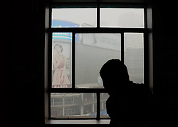 A visitor looks out of a window from the Feb. 7 Memorial Tower in Zhengzhou, capital of central China s Henan Province, Jan. 16, 2013. Affected by a cold front, the haze which has lingered in most parts of Henan for the past two weeks will begin to disperse on Jan. 17, 2013, according to the meteorological authority, China, January 16, 2013. Photo by Imago / i-Images...UK ONLY