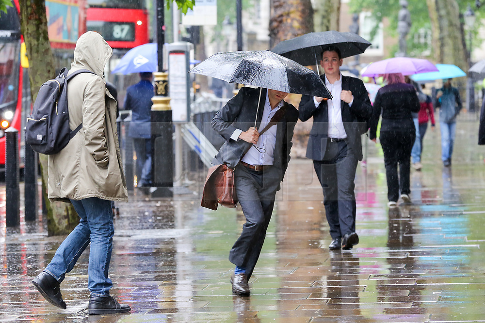 © Licensed to London News Pictures. 10/06/2019. London, UK. People shelter from the rain beneath umbrellas as rain falls in the capital. The Met Office has issued an amber warning for more rain, covering London and parts of southeast England later today Photo credit: Dinendra Haria/LNP
