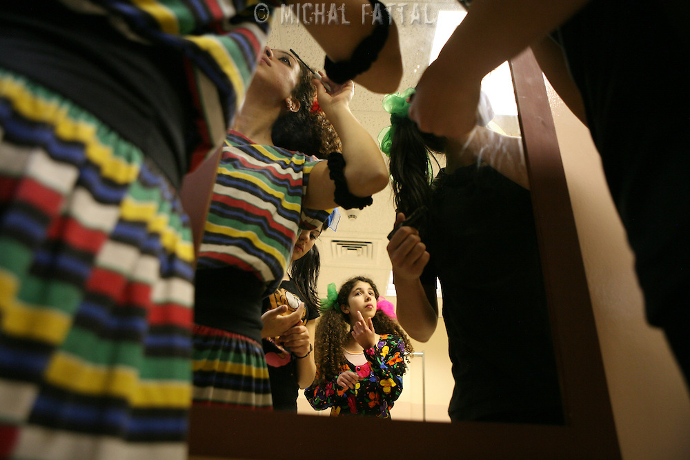 "Members of The Palestinian Circus School put on their make up behind the scenes, before going on stage to perform the show ""Circus behind the wall"" in Ramallah, November 20, 2009.The circus group was established in 2006, in order to give a new way of expression for Palestinians, and a new way to deliver the idea of resistance to the occupation. This performance is based on the life of Palestinians behind the separation wall. Photo by Michal Fattal/backyard"