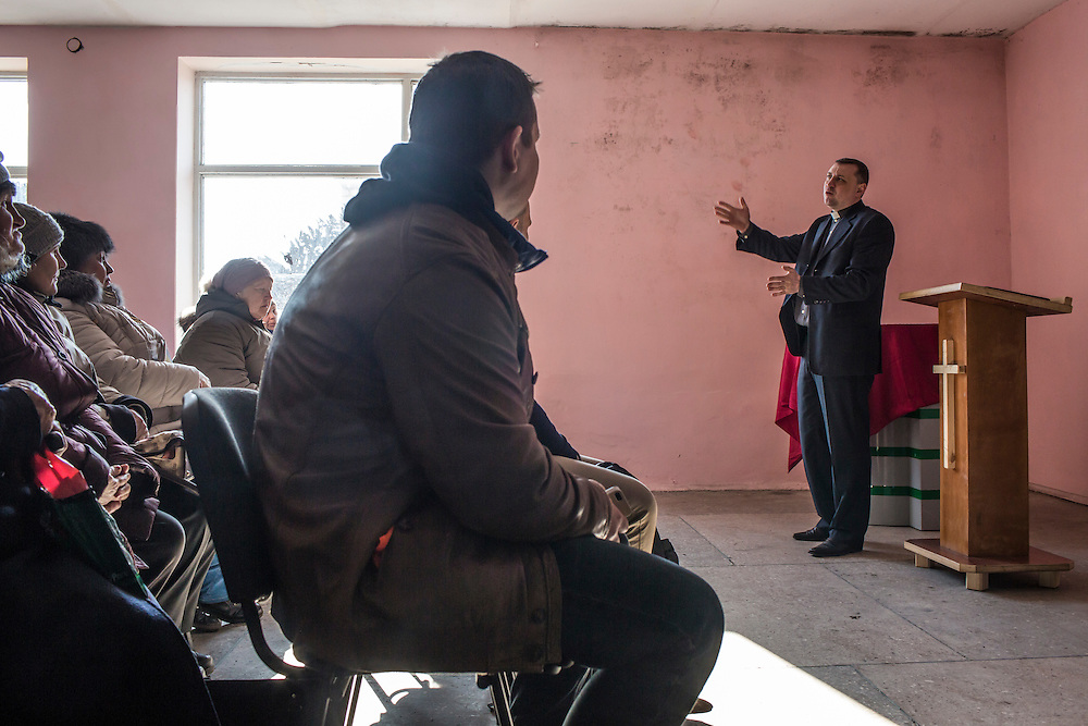 MARIINKA, UKRAINE - FEBRUARY 20, 2016:  Pastor Sergei Kosyak, right, leads a service at the Christian Help Center of the Church of the Transfiguration in Mariinka, Ukraine. The Donetsk suburb has been the scene of some of the heaviest fighting recently between Ukrainian forces and pro-Russian rebels. CREDIT: Brendan Hoffman for The New York Times
