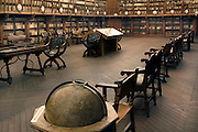 """Low angle view of Old Library, University of Salamanca,  Salamanca, Spain, pictured on December 18, 2010. Thousands of Antiquarian books line the shelves around the walls of the library. original furniture stands around the parquet floor, and in the foreground is a huge antique globe. Salamanca, an important Spanish University city, is known as La Ciudad Dorada (""""The golden city"""") because of the unique golden colour of its Renaissance sandstone buildings. Founded in 1218 its University is still one of the most important in Spain. Around it the Old Town is a UNESCO World Heritage Site. Picture by Manuel Cohen"""