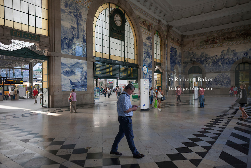 Travellers pass beneath traditional Azulejo tiles inside the ornate Sao Bento railway station in Porto, Portugal.