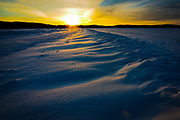 February sunset on windblown snow formations, on frozen Lake Inari. Inari, Lapland, Finland