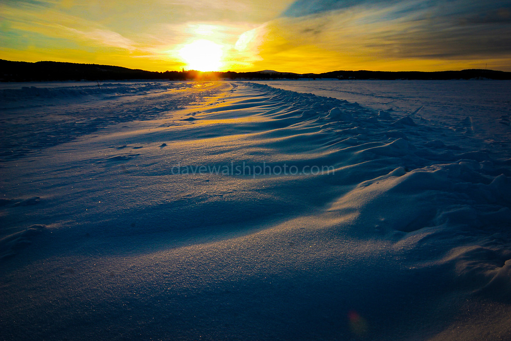 February sunset on windblown snow formations, on frozen Lake Inari. Inari, Lapland, Finland