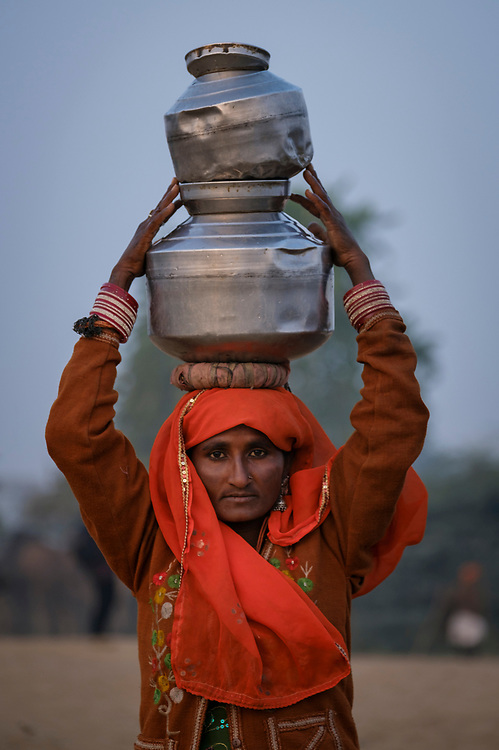 PUSHKAR, INDIA - CIRCA NOVEMBER 2016: Indian woman carrying water at Pushkar Camel Fair. It is one of the world's largest camel fairs. Apart from the buying and selling of livestock, it has become an important tourist attraction.