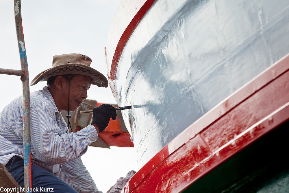 Sept. 24, 2009 -- PATTANI, THAILAND: THAN TRACHOWANICH, 52 years old, paints registration numbers on the side of a fishing boat being rebuilt in Siriudom Shipyards in Pattani, Thailand. Fishing is the main industry in Pattani, one of just three Thai provinces with a Muslim majority. Thousands of people, mostly Buddhist Thais and Burmese Buddhist immigrants, are employed in the fishing industry, either crewing ships, working in processing plants or working in the ship building and refreshing yards.   Photo By Jack Kurtz