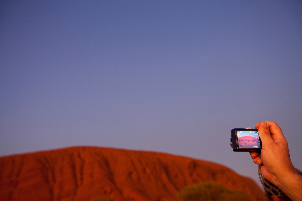 Australia, Northern Territory, Uluru - Kata Tjuta National Park, Tourist takes snapshots of Ayers Rock  before sunrise