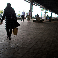 A women with bags walking toward pier 11 ferry terminal downtown New York City