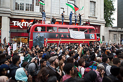 Image ©Licensed to i-Images Picture Agency. 11/07/2014. London, United Kingdom. Demonstration in London against Israeli strikes in Gaza. Central London. Protesters on top of a double decker busin a demonstration against Israeli strikes in Gaza outside the Israeli Embassy in London. Picture by Daniel Leal-Olivas / i-Images