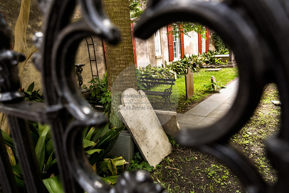 A tombstone rests on a palm tree in the garden of the French Huguenot Church along Queen Street in historic Charleston, SC.