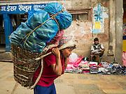 06 AUGUST 2015 - KATHMANDU, NEPAL: A man carries cucumbers to a market in Kathmandu.      PHOTO BY JACK KURTZ