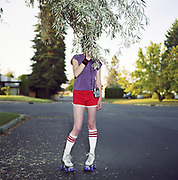 Young woman wearing roller skates on street, face obscured by branch