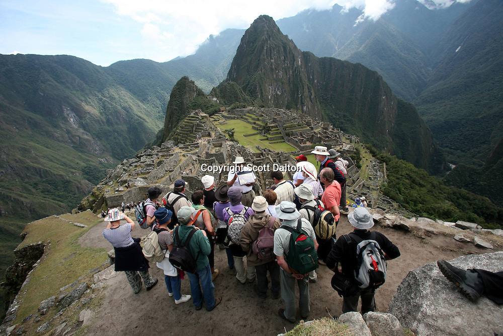 Tourists listen to a guide while on a tour of the lost Inca city of Machu Picchu in Peru, on August 11, 2007. Machu Picchu was recently voted one of the new Seven Wonders of the World. Some experts are concerned if the site can maintain the large number of tourists that visit the site and are worried that if proposals to increase the number of visitors will have adverse effects on the ancient ruins. (Photo/Scott Dalton)
