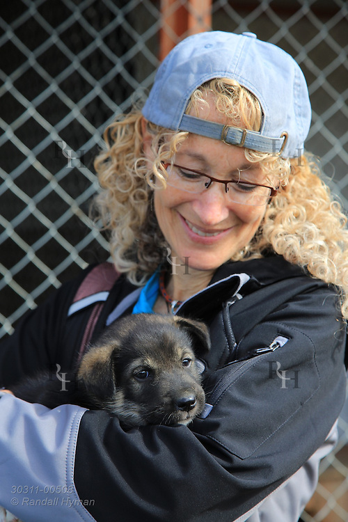 Writer Susan Zimmerman carries puppy on its first summer outing away from mother at the Tromso Villmarkssenter sled dog center on Kvaloya Island outside Tromso, Norway.